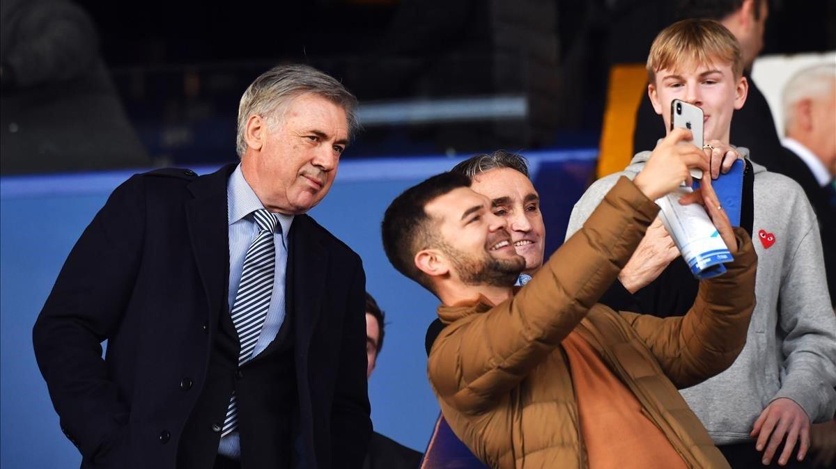 Carlo Ancelotti posa pra una foto con un fan del Everton en la grada de Goodison Park.