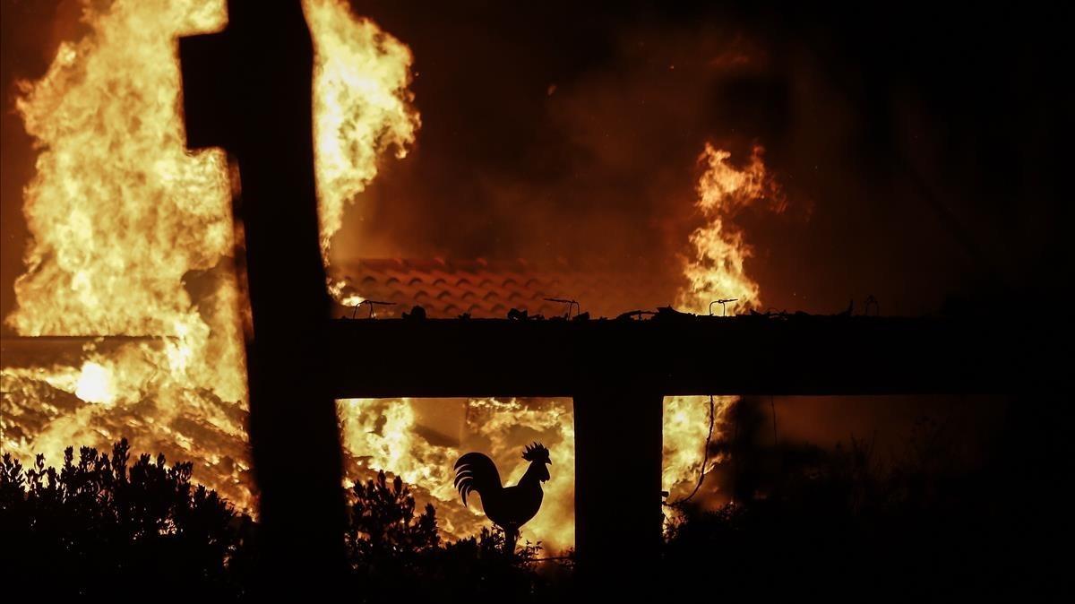 El fuego arrasa un jardín de una casa en Mati, un suburbio al noreste de Atenas.