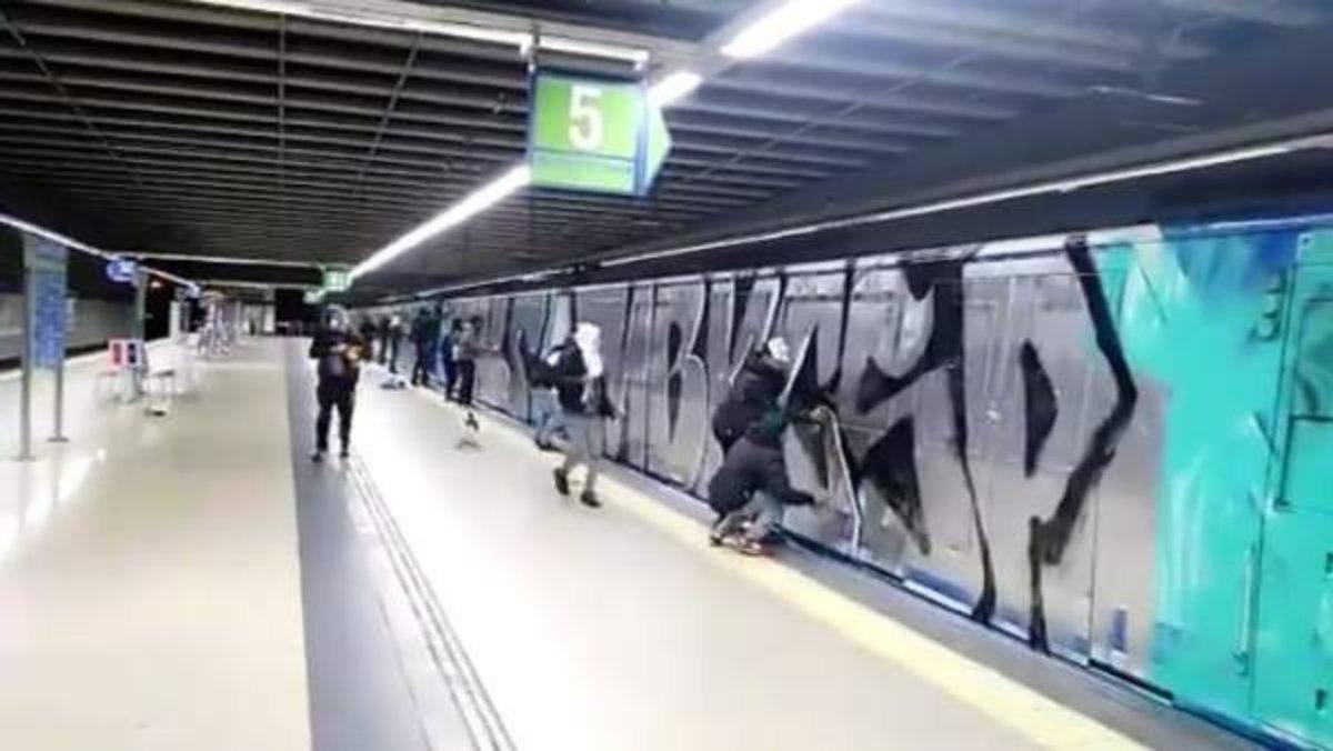 Grafiteros pintan vagones del Metro de Madrid.