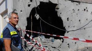 Un israelí inspecciona una casa dañada en la franja de Gaza