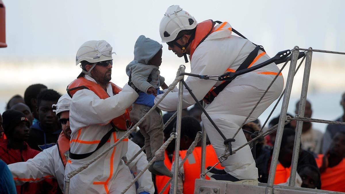 Equipos de rescate sostienen a un menor llegado en patera.