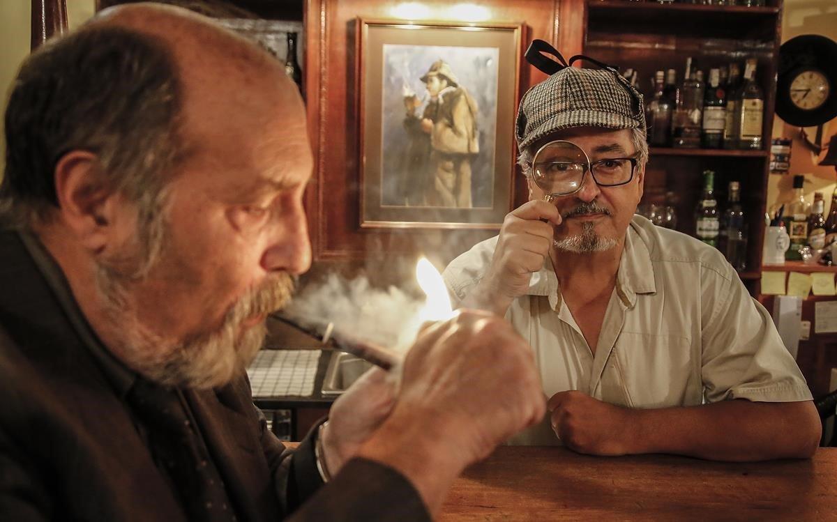 Ojeda (Harold Stackhurst), con gorra y lupa holmesianos en el Pipa Club.