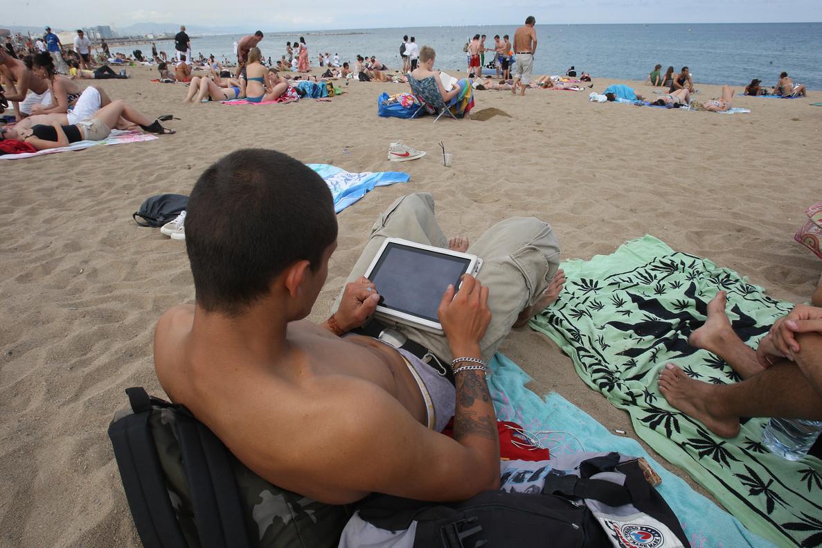 Un joven, con una tablet en la playa de la Barceloneta, en julio.