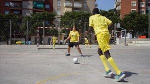 Jóvenes jugadores juegan en una cancha de cemento en Mataró