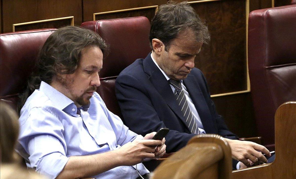 Pablo Iglesias y Jaume Asens consultan sus móviles en el segundo día del debate de investidura de Pedro Sánchez.