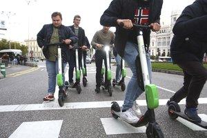 Un grupo de extranjeros utilizan el patinete eléctrico en la calle Alcalá de Madrid.