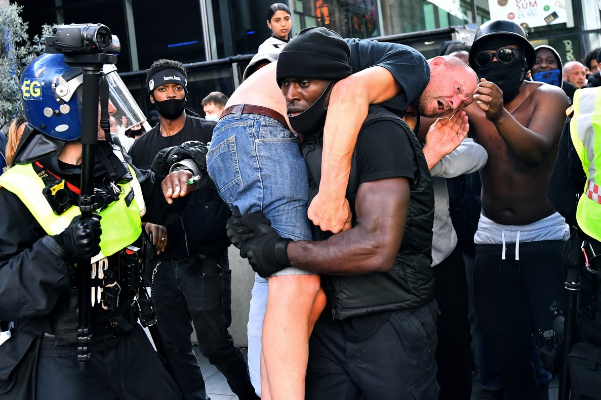 Patrick Hutchinson, a protester, carries a suspected far-right counter-protester who was injured, to safety, near Waterloo station during a Black Lives Matter protest following the death of George Floyd in Minneapolis police custody, in London, Britain, June 13, 2020. REUTERS/Dylan Martinez TPX IMAGES OF THE DAY SEARCH INJURED COUNTER-PROTESTER FOR THIS STORY. SEARCH WIDER IMAGE FOR ALL STORIES.
