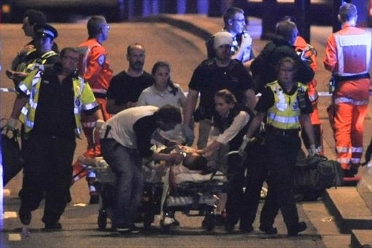 Policías y miembros de los servicios de emergencias atienden a una de las víctimas del puente de Londres.