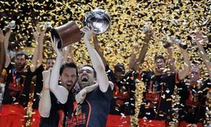 Rafa Martínez y Van Rossom alzan el trofeo ante el resto de jugadores del Valencia Basket.
