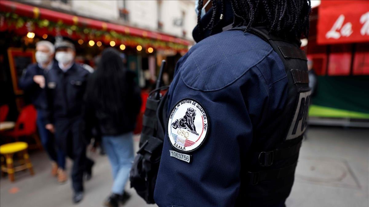 Un policía del cuerpo 'Grupo de Seguridad de Proximidad', vigila este martes que se cumplan las nuevas medidas de prevención y resticciones para frenar la expalsión del covid-19 en París.