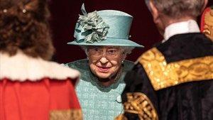 La reina Isabel II habla con unos oficiales antes de pronunciar su discurso, este jueves en Londres.