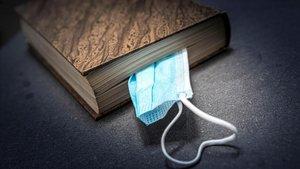 Una mascarilla entre las hojas de un libro