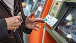Una usuaria muestra una tarjeta T-usual que acaba de adquirir.