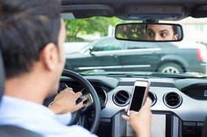 Un conductor, con un móvil.