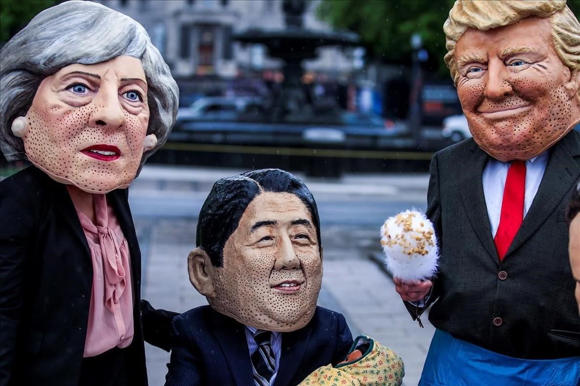 Tres activistas con las caretas de Trump, Theresa May y Shinzo Abe, en Canadá.