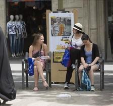 Turistas de compras en el centro de Barcelona ajenos a la campaña electoral que denotan los cartelessituados a sus espaldas.