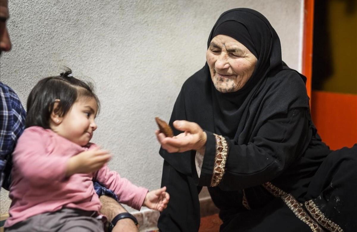 Una anciana siria juega con una niña en la casa de una familia refugiada en Barcelona.