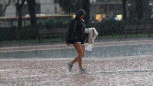 Una joven bajo la lluvia en plaza Catalunya de Barcelona, en una imagen de archivo.