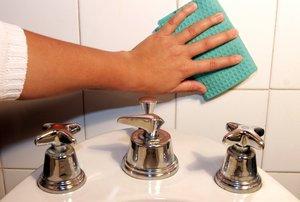 Una mujer limpia las baldosas de un baño.