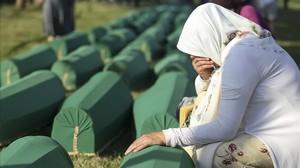 Una mujer llora junto a una de las nuevas víctimas identificadas de Srebrenica.