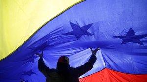 Una mujer sujeta una gran bandera de Venezuela.