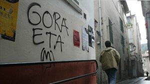 Una persona junto a un graffiti proetarra.