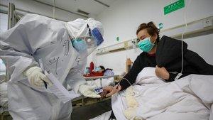 Un médico examina a un paciente con coronavirus en el hospital de Wuhan, este jueves.