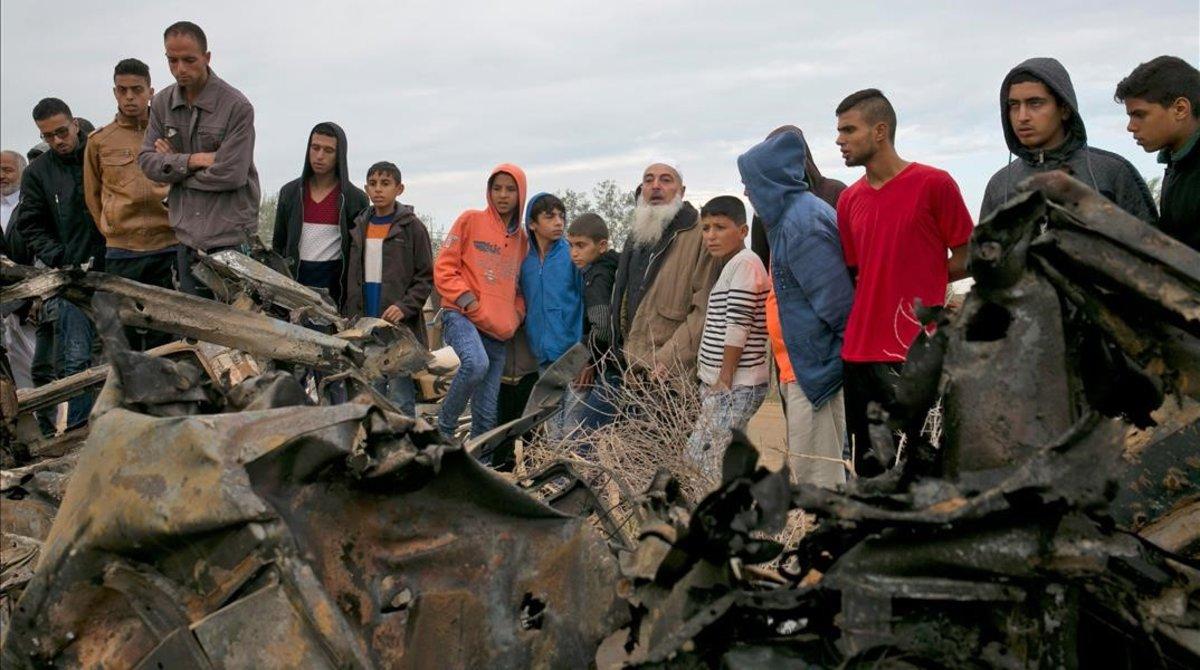 Unos palestinos permanecen junto a los restos de un automóvil destruido tras un ataque aéreo israelí en Khan Yunis, en el sur de la Franja de Gaza.