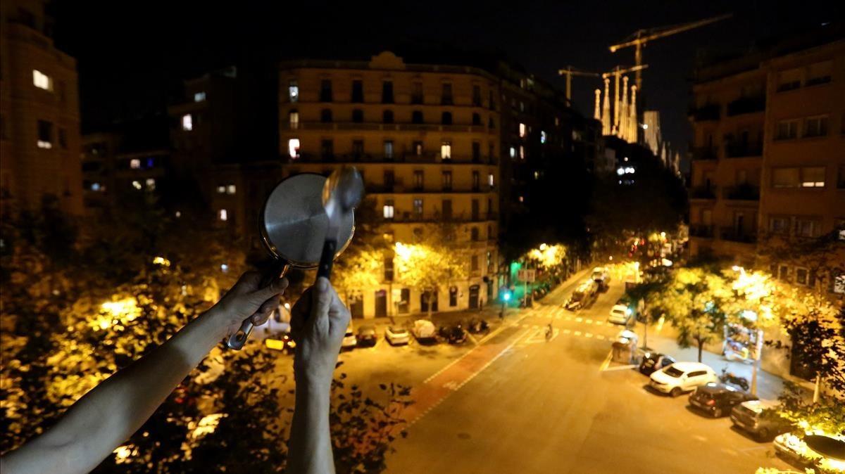 Un veí del barride la Sagrada Famíliasurt al balcó perparticipar en la cassolada.