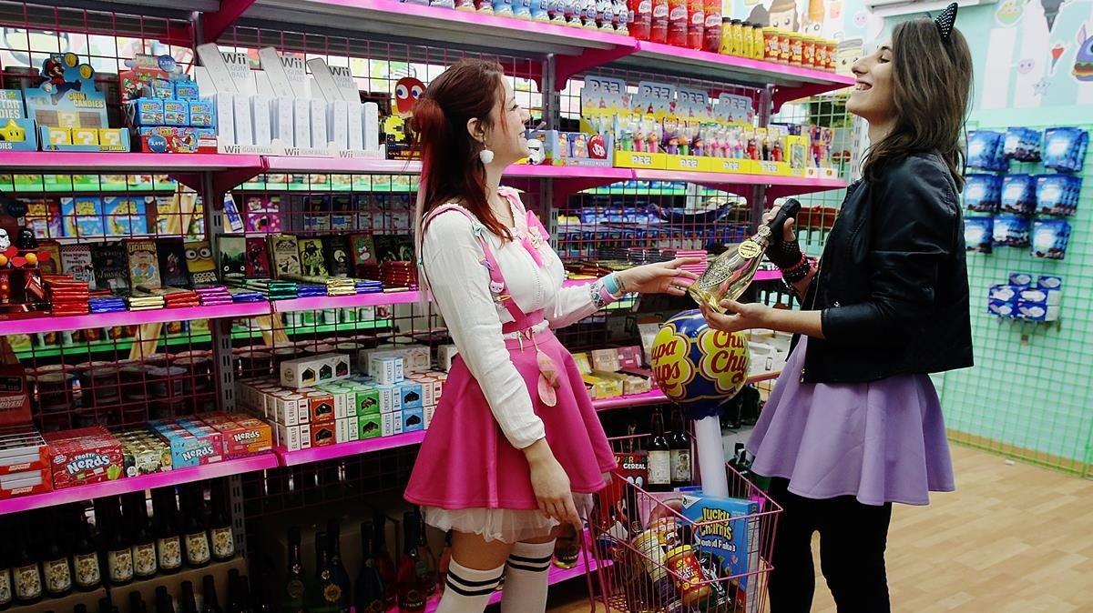 Miriam y Soraya, dos de las dependientas delSuper Friki Market, en las Galeries Maldà,con uncarrito rosa lleno de productos. Soraya tiene en las manos un cava con oro comestible.