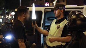 Un guardia urbanocomprueba si un conductor puede haber tomado drogas, la madrugada del sábadoen la Gran Via.