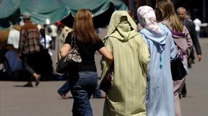 Mujeres vestidas al uso occidental junto a otras con vestimentas tradicionales, en la plaza Jemaa El Fna, en Marraquech, en una imagen de archivo.