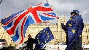 Un contrario al 'brexit' ondea una bamdera británica junto a otra de la Unión Europea frente al Parlamento británico.