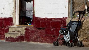 Un coche de bebé a las afueras de una casa-barraca en Poblenou.