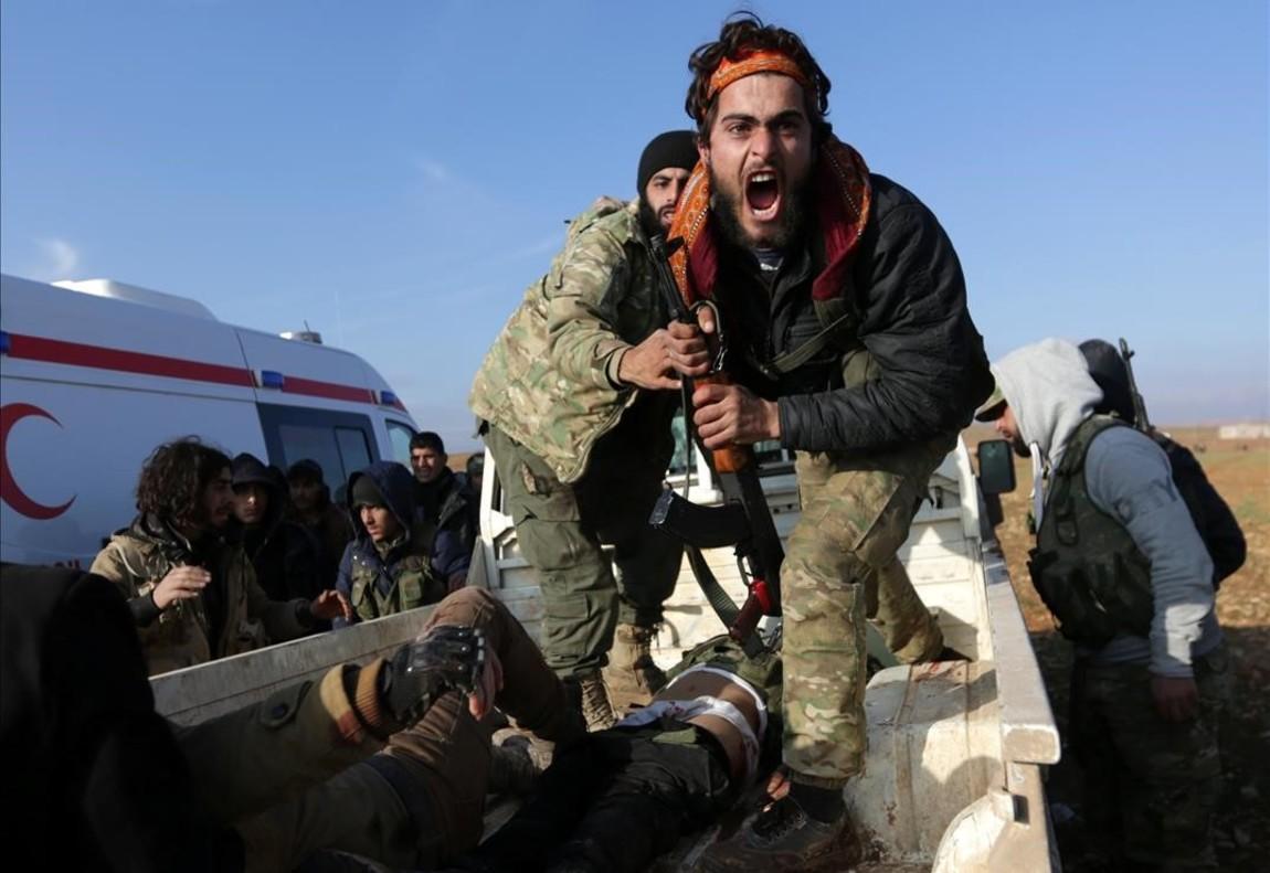 Un combatent de l'Exèrcit sirià lliure es lamenta a prop del cos del seu germà, que va morir durant una ofensiva contra els combatents de l'Estat Islàmic per agafar el control de la ciutat de Qabasin (Síria).