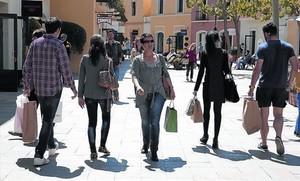 Compradores paseando por las calles de La Roca Village, ayer.