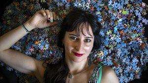 Elisabeth Guajardo, sobre una cama compuesta por las piezas de sus puzles.