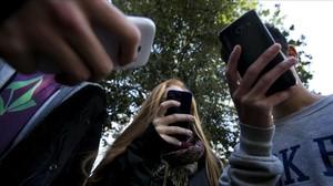 Unos adolescentes utilizan su teléfono móvil.