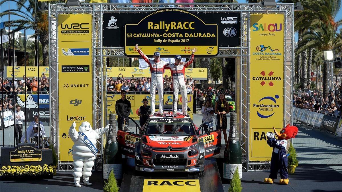 Kris Meeke (derecha) y su copiloto Paul Nagle celebran el triunfo en el Rally de Catalunya sobre el capó de su Citroën.