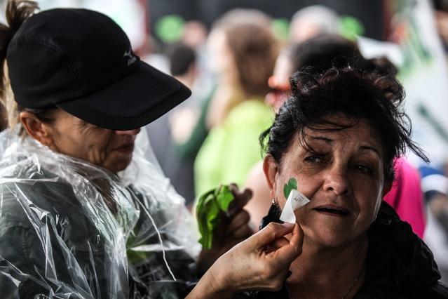 Una mujer pone un dibujo de un corazón verde, en la playa de Ipanema, durante la marcha contra contra el cambio climático.