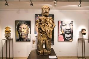 Un muñeco fetiche de los Bakongo, entre dos telas contemporáneas de Médéric Turay.
