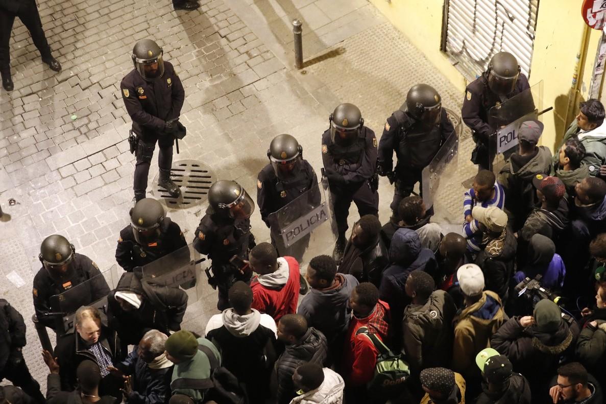 GRAF3166 MADRID 15 03 2018 - Policias antidisturbios intentan calmar la tension en la calle Meson de Paredes con la calle del Oso en el barrio de Lavapies de Madrid tras la muerte de un mantero de un paro cardiaco durante un control policial contra el top manta en el barrio de Lavapies de Madrid Tras el suceso se han concentrado decenas de personas en protesta contra la presion policial que existe en la zona contra los vendedores del top manta EFE JAVIER LIZON