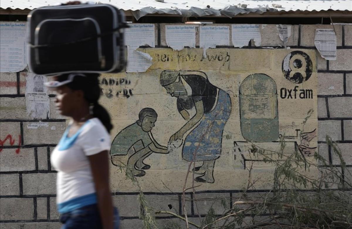 Una mujer en Haití, frente a un mural de Oxfam.