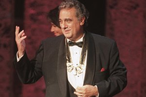 FILE - In this Tuesday, Sept. 14, 1999 file photo, Placido Domingo acknowledges the audience after receiving the 1999 Hispanic Heritage Award at the John F. Kennedy Center for the Performing Arts in Washington. An evening before a performance of âLe Cid,â part of the Washington Operaâs 1999-2000 season, opera singer Angela Turner Wilson said she and Domingo were having their makeup done together when he rose from his chair, stood behind her and put his hands on her shoulders. As she looked at him in the mirror, he suddenly slipped his hands under her bra straps, she said, then reached down into her robe and grabbed her bare breast. It hurt, she told The Associated Press. âIt was not gentle. He groped me hard.â She said Domingo then turned and walked away, leaving her stunned and humiliated. (AP Photo/Leslie Kossoff)