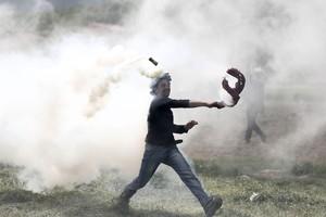 Un refugiado lanza de vuelta un bote de gas lacrimógeno durante una protesta en el campo de refugiados de Idomeni, situado en la frontera entre Macedonia y Grecia.