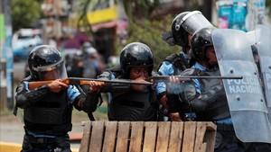 Dos agentes apuntan a los manifestantes en una de las protestas en Managua.