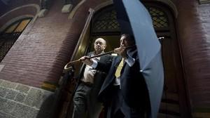 Félix Millet abandona el Palau de la Música por la puerta de atrás tras el registro de las oficinas, el 23 de julio del 2009.