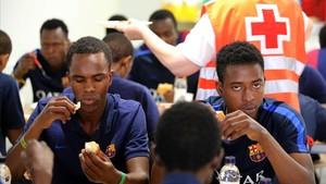 Jóvenes inmigrantes procedentes de Guinea, atentidos en el centro de acogida de emergencias del pasaje del Dos de Maig.