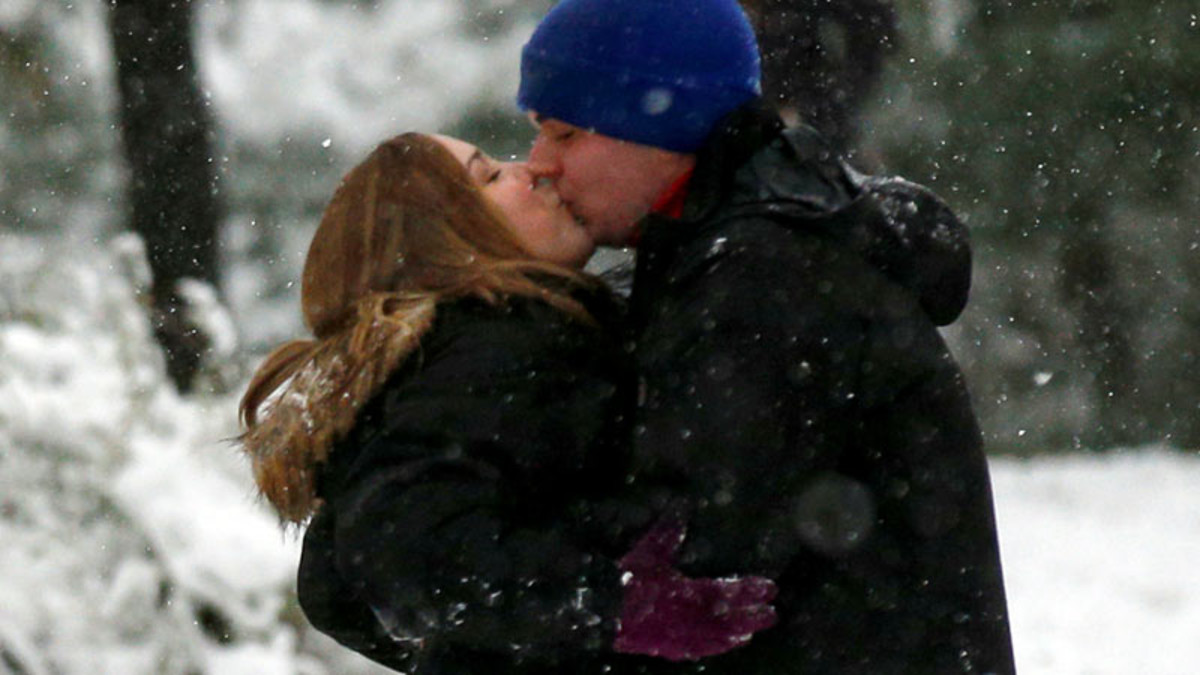 Una pareja se besa en un parque de Nueva York en plena nevada.