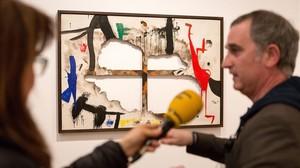 Tela quemada 1, de Joan Miró,en la exposición Autogestión, en la Fundació Miró, con el comisario de la misma, el artista Antonio Ortega.